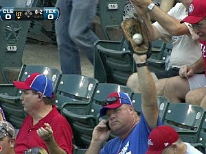 Fan grabs foul ball while on phone